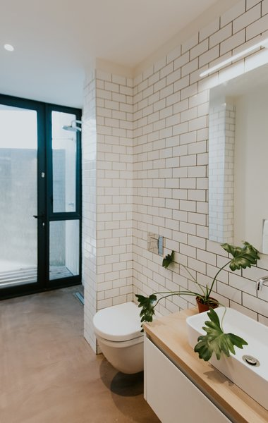 Simple subway tiles decorate the walls of the main floor bath. A seamless concrete floor leads to directly to the shower with full-height glazing.