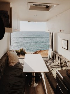The two benches on each side of the table converted into the couple's bed. When they parked the vehicle, they would open the doors to allow the living space to merge with the outdoors.