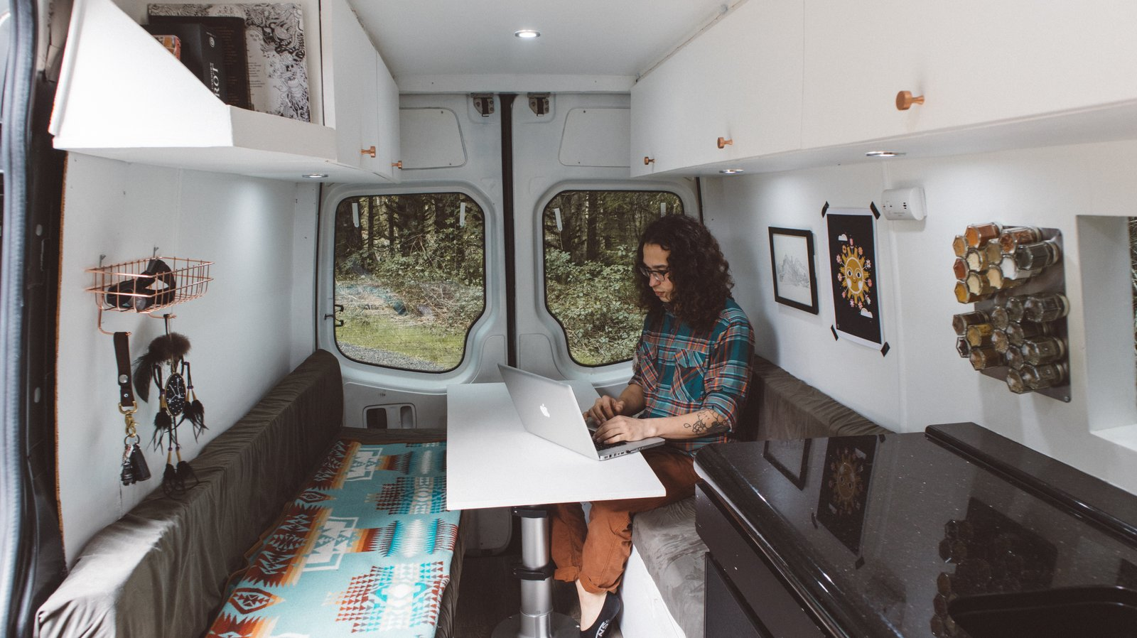 Dining Room, Bench, Table, and Recessed Lighting The interior of the van incorporated the couple's personal style. Artwork and blankets also reflected their artistic aesthetic.    Photo 9 of 12 in These Digital Nomads Live, Work, and Travel in a Sprinter Van