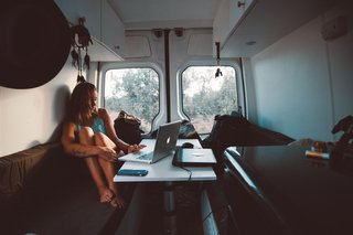 In their old van, the bench and table served as the ideal workspace for the traveling couple.