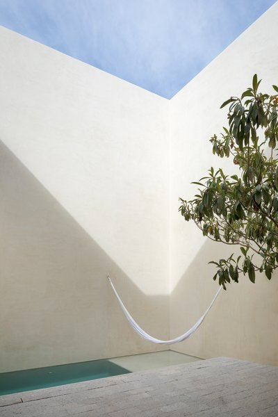 During the day, light and shadows create abstract forms along the facades of the courtyard, providing different perspectives as the sun passes over.