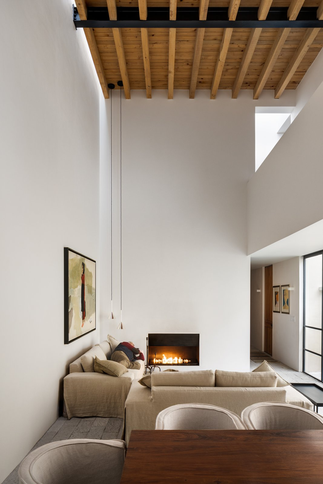 Living Room, Standard Layout Fireplace, Pendant Lighting, and Sofa In the main living space, two sofas are arranged around a fireplace, with long pendant lights hanging from the high ceiling.    Photo 5 of 9 in What it Really Means When a Home Has Good Bones from Muted Tones Mingle With Light and Shadows to Form a Quiet Mexican Oasis