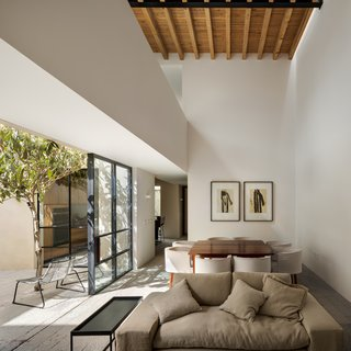 An open walkway between the bedrooms spans across the open living space, revealing the wood rafters above.