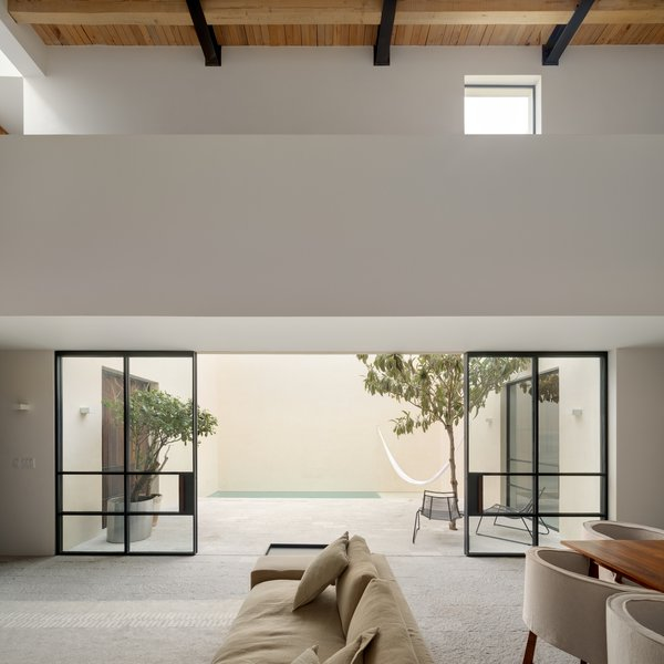 Sliding glass doors provide a seamless connection between the interior and outdoor spaces. Green vegetation dots the courtyard, drawing the colors of nature inward.