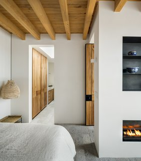 The minimal, modern character extends into the bedrooms. Simple steel shelves are embedded in the wall above a linear fireplace. A rattan pendant hangs above the nightstand.
