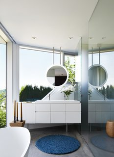 In the master bath, a geometric mirror hangs from the ceiling above, providing continuous views to the hills and sky beyond.