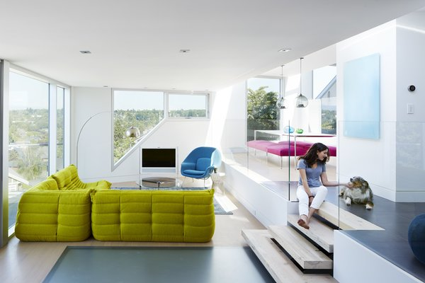 In the main living space, brightly colored furnishings—including an iconic womb chair and a sofa from Ligne Roset—create a playful interior space for lounging. A laminated glass floor allows light to pass further between the various levels.