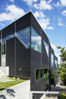 As you can see, the home follows the slope of the land.  Geometric punched window openings draw in plentiful daylight.
