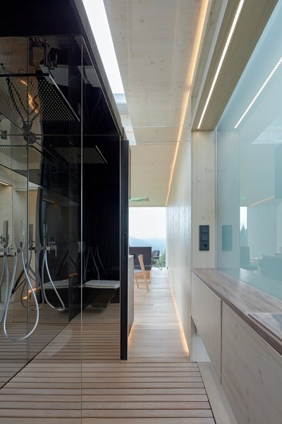 Seamless transitions occur between spaces. A frosted glass window allows daylight to fall into the bath space, while also providing privacy.