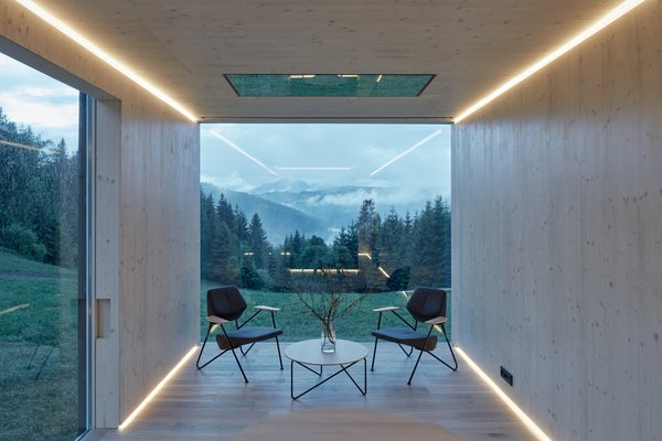 The birch-clad interior frames views of the outside settings. Strip lights along the exterior walls provide directional focus outward.