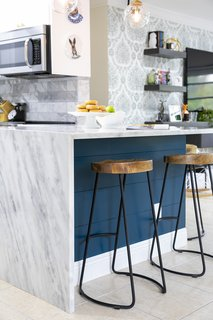 A continuous waterfall edge of the marble countertops creates an impactful statement at the peninsula. Iron and wood bar stools are an industrial accent in the chic space.
