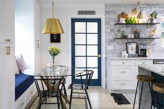 The  newly expanded laundry room is accessible via a blue door, directly adjacent to the kitchen and dining spaces.