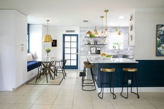 In the open kitchen-dining combo, deep blue colors, brass accents, and marble textures blend to create a contemporary aesthetic.