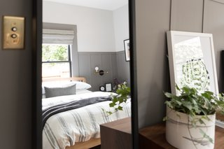 The large, metal framed mirror allows daylight from the window to reflect within the space. The brass-plated light switch is a reproduction authentic to the original era of the home.