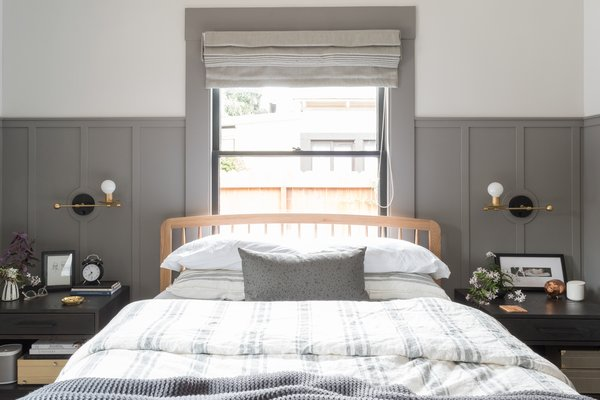 Centrally located under the window, the bed now has equal spacing on either side, allowing just enough space for matching nightstands and wall sconces. The shades are a combination of roman blackout shades and light-diffusing solar shades from SelectBlinds.