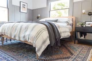 A wool vintage rug from eSaleRugs its below the light oak bed-frame from Article. The sheets are an organic sheet set from Target, adorned by a natural linen duvet cover, and pillow shams and oversized throw from Pom Pom at Home.