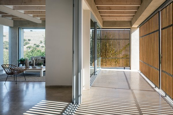 The main living spaces open directly onto a grand exterior patio shaded by wooden screens.