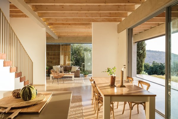 Exposed wooden beams draw in the natural elements. Furnishings and textiles are composed of similar materials, creating a subdued and relaxed interior palette.
