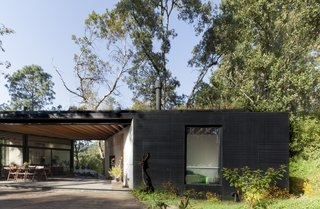 At the center of the home lies an open-air gathering space covered by the wood framed roof above.