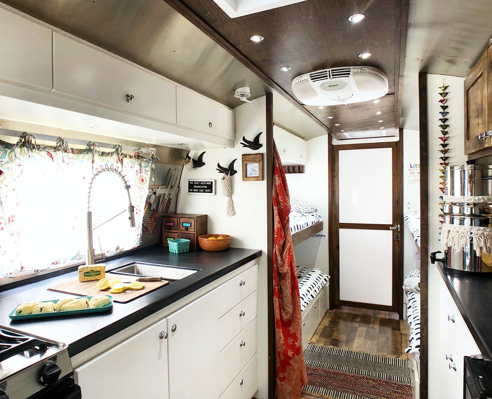 Kitchen, White Cabinet, Undermount Sink, Range, and Medium Hardwood Floor In the kitchen, there is plenty of counter space and storage.    Photo 5 of 12 in A 1970s Airstream Is Revamped Into an Off-Grid Home For Six from 1972 Vintage Airstream Trailer