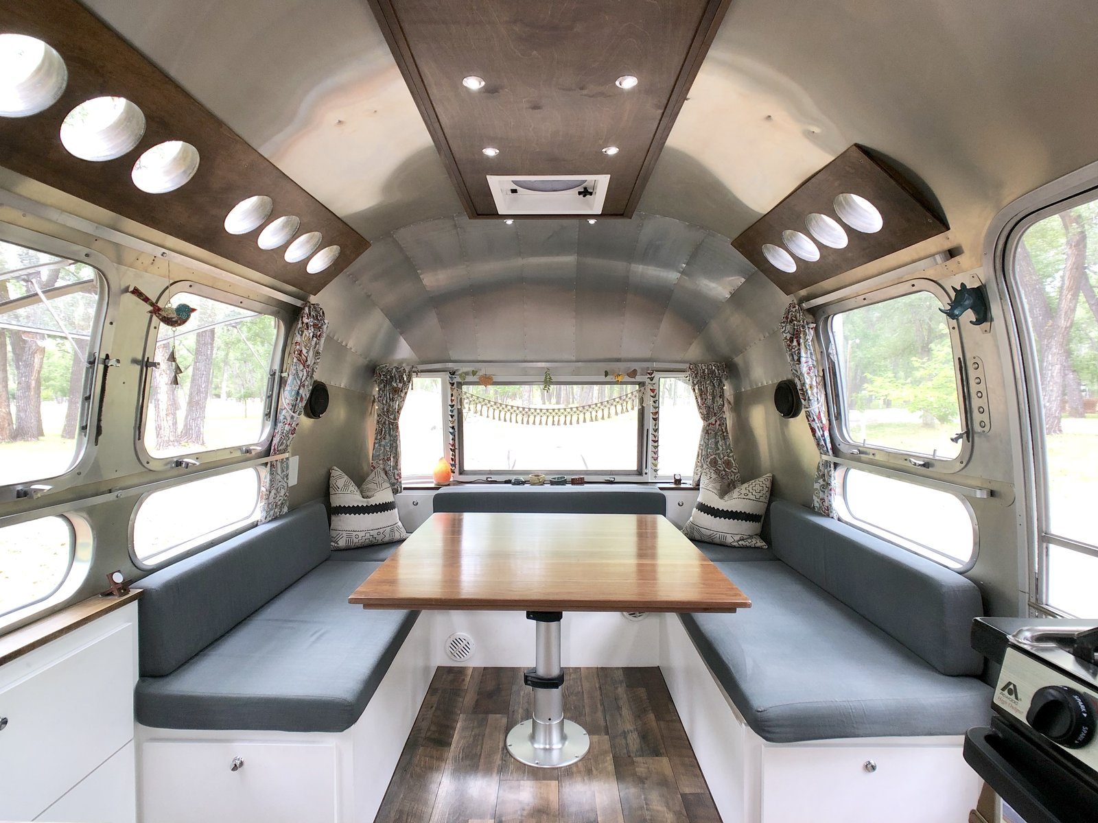 Dining Room, Table, Medium Hardwood Floor, and Bench A large dining space provides enough room for the family to comfortably dine, work, and play games. Curtains from their previous home have been repurposed for this new space.    Photo 8 of 12 in A 1970s Airstream Is Revamped Into an Off-Grid Home For Six from 1972 Vintage Airstream Trailer