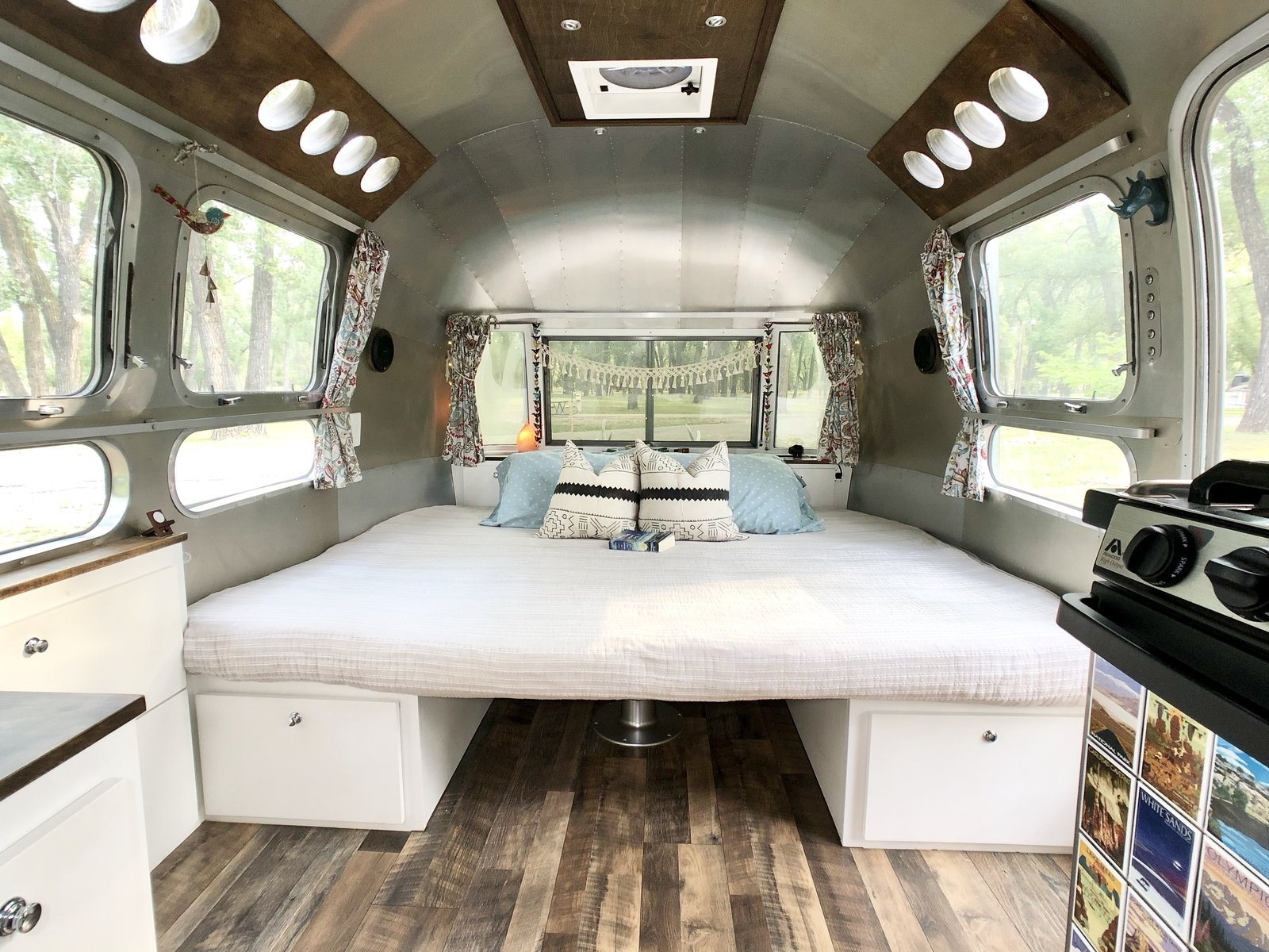 Bedroom, Medium Hardwood Floor, Storage, and Bed The dinette space can completely transform into an almost king-size bed.    Photo 9 of 12 in A 1970s Airstream Is Revamped Into an Off-Grid Home For Six from 1972 Vintage Airstream Trailer