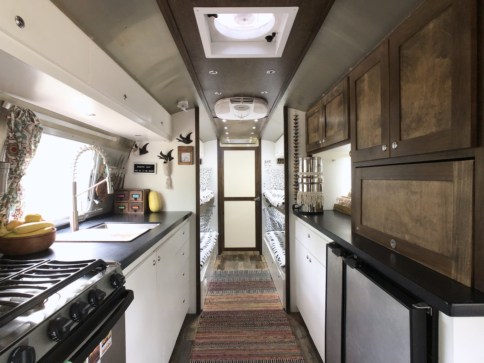 Kitchen, Medium Hardwood Floor, Undermount Sink, Refrigerator, White Cabinet, and Range A neutral color palette is combined with wood flooring and cabinetry to provide warmth in the airy interior space.    Photo 4 of 12 in A 1970s Airstream Is Revamped Into an Off-Grid Home For Six from 1972 Vintage Airstream Trailer