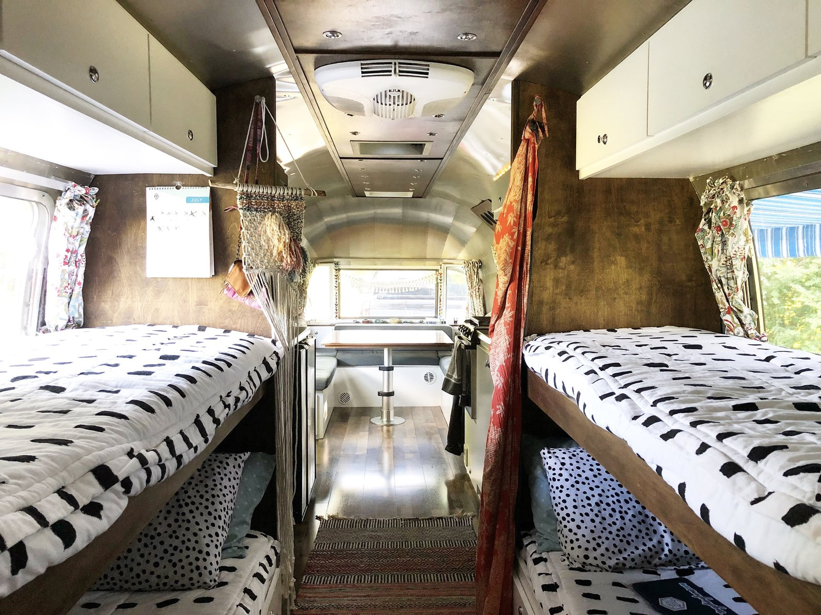 Bedroom, Bunks, and Medium Hardwood Floor A look at the double bunk-beds that can convert into couches when not in use.    Photo 7 of 12 in A 1970s Airstream Is Revamped Into an Off-Grid Home For Six from 1972 Vintage Airstream Trailer