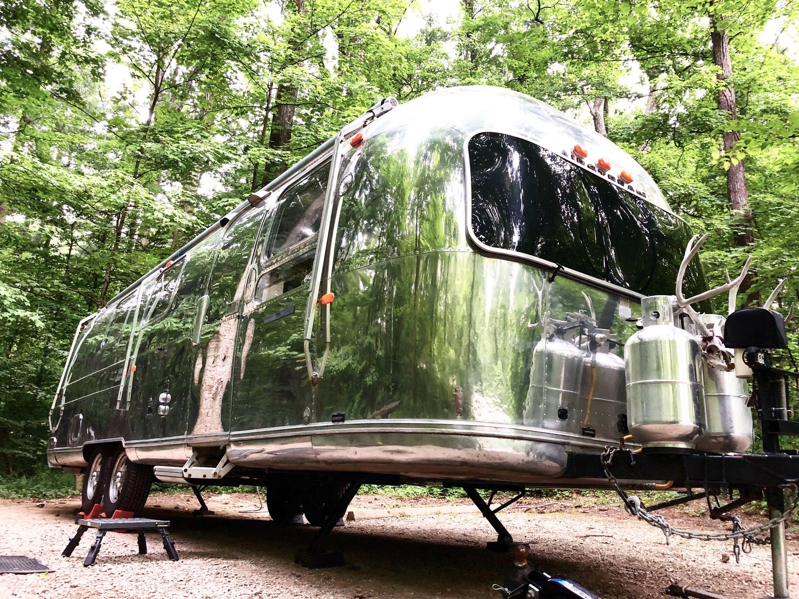 Exterior and Airstream Building Type The shiny aluminum exterior screams vintage classic. Yet on the interior, modern touches and stylish decor transform vintage into chic.    Photo 3 of 12 in A 1970s Airstream Is Revamped Into an Off-Grid Home For Six from 1972 Vintage Airstream Trailer