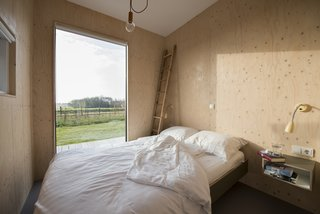 Bedrooms are adorned with the same simple material palette.  Wood clad walls, white ceilings, large windows, and simple pops of color allow the views to remain as the focal point.