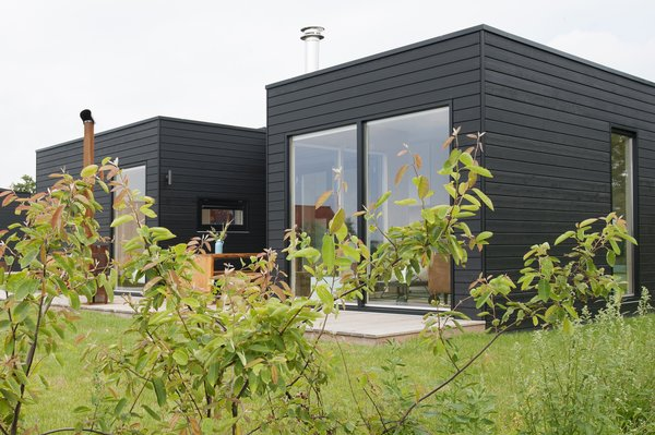 Clad in black-washed decking, the simple structure makes a quiet statement in the natural setting. While its thoughtful layout provides plenty of space for family gatherings, the cabin is also an idlliic setting for a private hideaway.