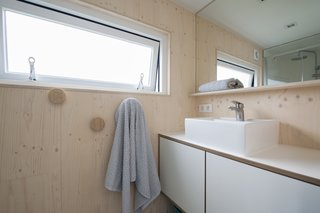 The bath is complete with a floating vanity, vessel sink, walk-in shower, and large mirror.