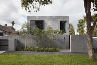 The exterior is composed of a rigid grid of Bluestone cladding that wraps the exterior facades.