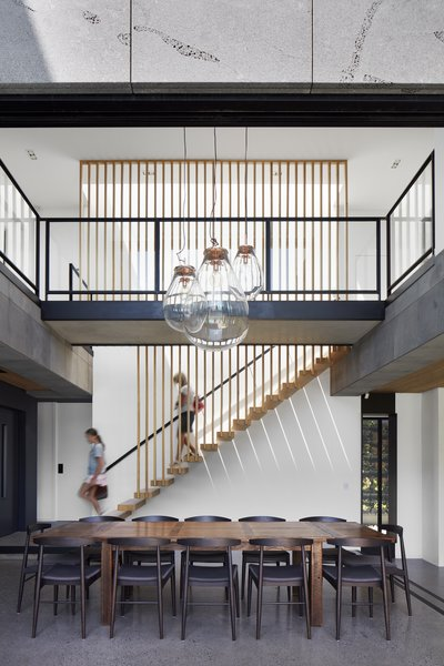 Vertical wood slats continue from the stair treads to the ceiling, emphasizing the openness and grandeur of the open, two-story dining space.