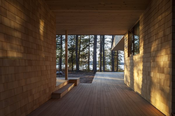 The textured facade playfully displays light and shadows as the sun moves throughout the day and seasons. The framed breezeway reaches outward to the fjord.
