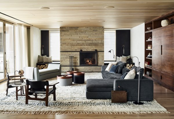 Large living spaces embody modern comfort.  A stone clad wood-burning fireplace, lush furnishings in rich colors, soft textiles, and custom built-ins create a retreat worth staying in.