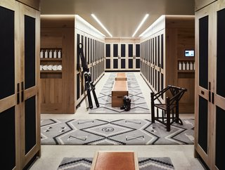 There is also a boot room and changing area for skiers, which features rustic wooden lockers, dark accents, and decorative rugs to continue to draw in the mountain style.