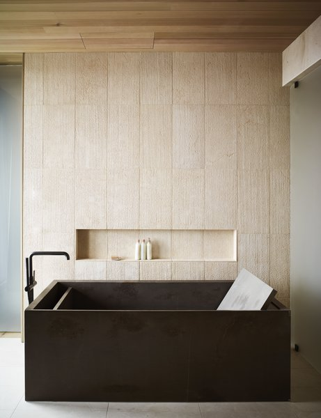 The rough texture of the tile walls adds a natural element to the refined, elegant bath.