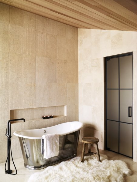 This private bath is a dream retreat after a long day exploring.  A tin soaker tub, lush fur rug, and large tiles in natural tones create an ideal, calming escape.