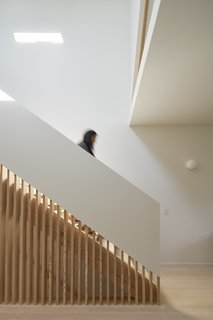 By incorporating wood slats into the stair wall, light from above is able to pass farther into the space between levels.