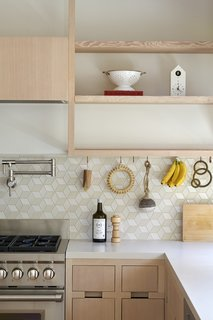 Open wooden shelving serve as an idyllic spot to display special kitchen gadgets and trinkets.