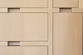 The custom wood joinery uniquely eliminates the addition of pulls through a recess in the cabinets. The whitewashed wood with a matte sealer is a sleek, modern finish that blends nicely with the wooden slats in the atrium.