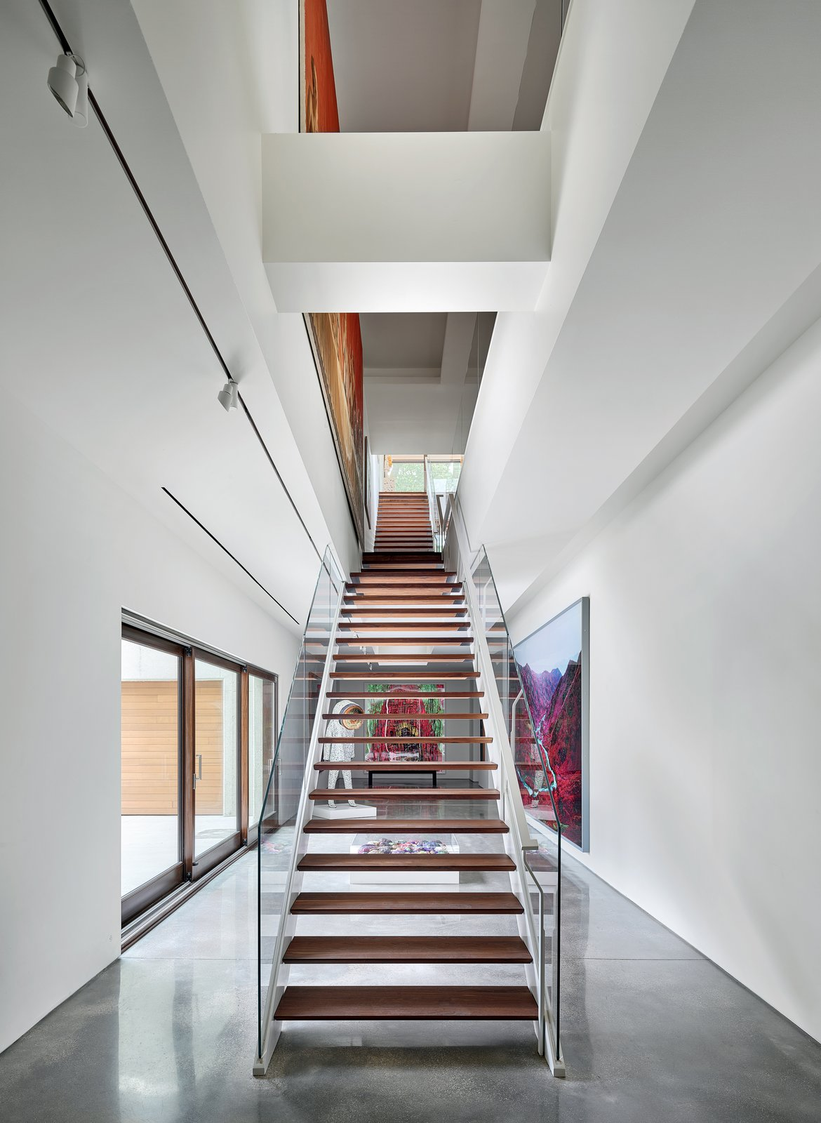 Staircase, Glass Railing, Wood Tread, and Metal Railing The long, wood stairs appear as a screen, quietly revealing artwork between levels and spaces.   Photo 10 of 23 in A Luminous, Eco-Friendly Abode Is Completed With its Own Modern Art Gallery from Artery House