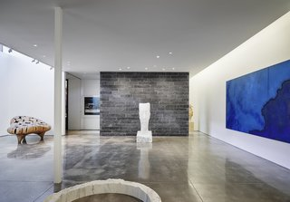 The below-grade gallery space much resembles a modern art gallery.  White walls and concrete floors provide the ideal backdrop for the curated collection of art, accented by indirect lighting.