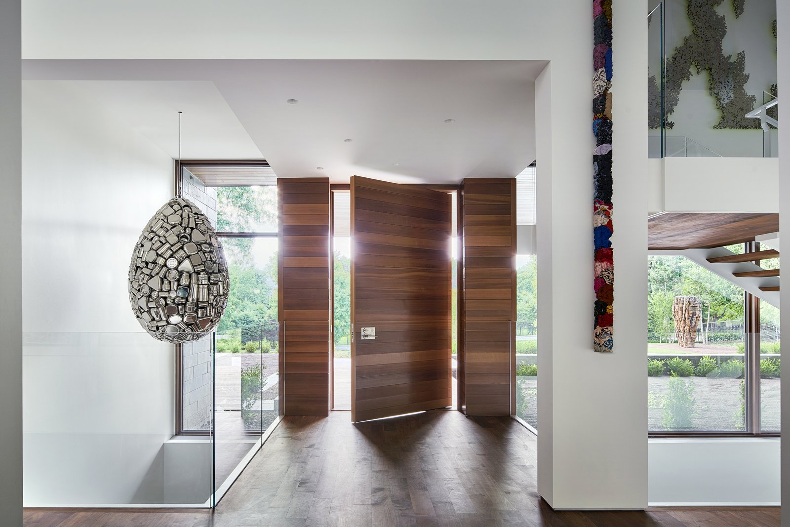 Hallway and Medium Hardwood Floor Upon entry, one passes over a bridge, immediately revealing the vertical and open nature of the home from above to below.  Artery House