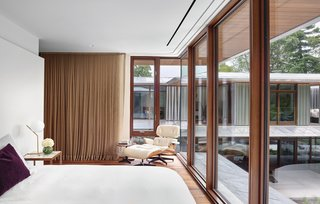 A Mahogany storefront system allows for grand views of the exterior landscape and sculpture garden.  A recessed track allows curtains to be drawn in times of sleep or privacy.