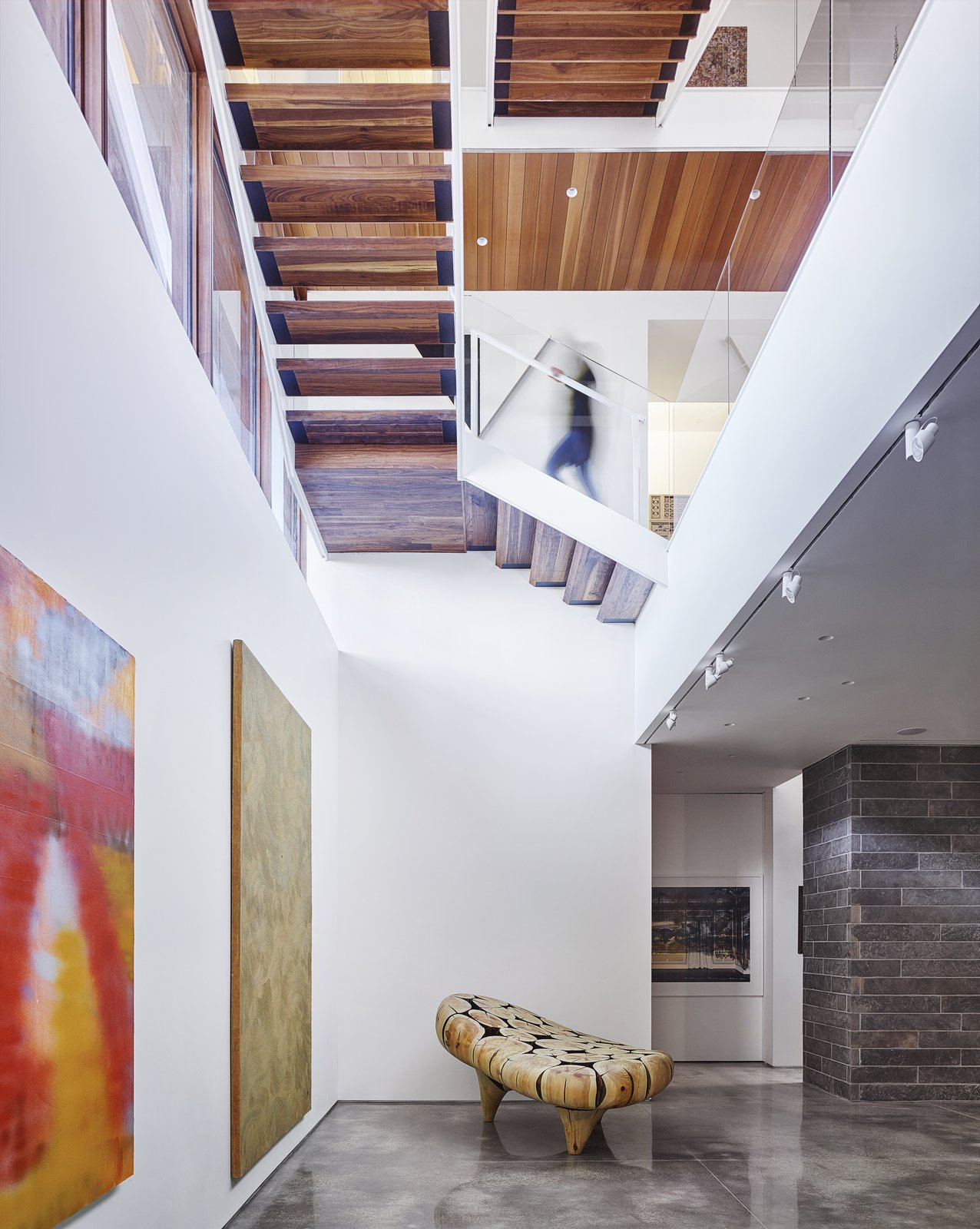 Hallway and Concrete Floor A open-tread staircase connects the below-grade gallery space to the living spaces above. Glass guardrails and the open treads allow for visual continuity and passage of light.    Artery House