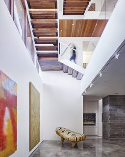 A open-tread staircase connects the below-grade gallery space to the living spaces above.  Glass guardrails and the open treads allow for visual continuity and passage of light.