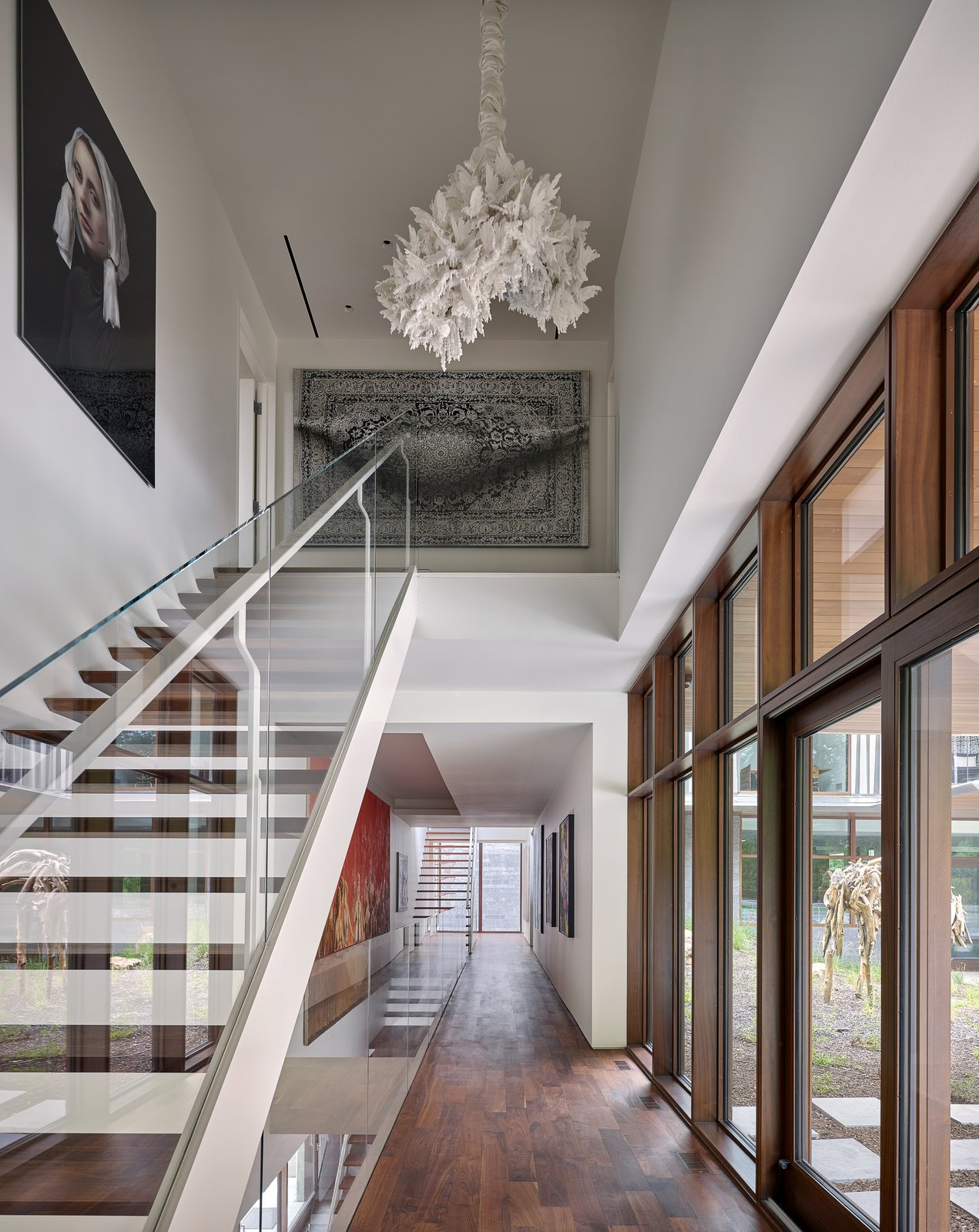 """Staircase, Glass Railing, Wood Tread, and Metal Railing Porosity and transparency define the """"arteries"""" that display artwork, connect the floors, and reveal moments of awe.   Photo 3 of 23 in A Luminous, Eco-Friendly Abode Is Completed With its Own Modern Art Gallery from Artery House"""