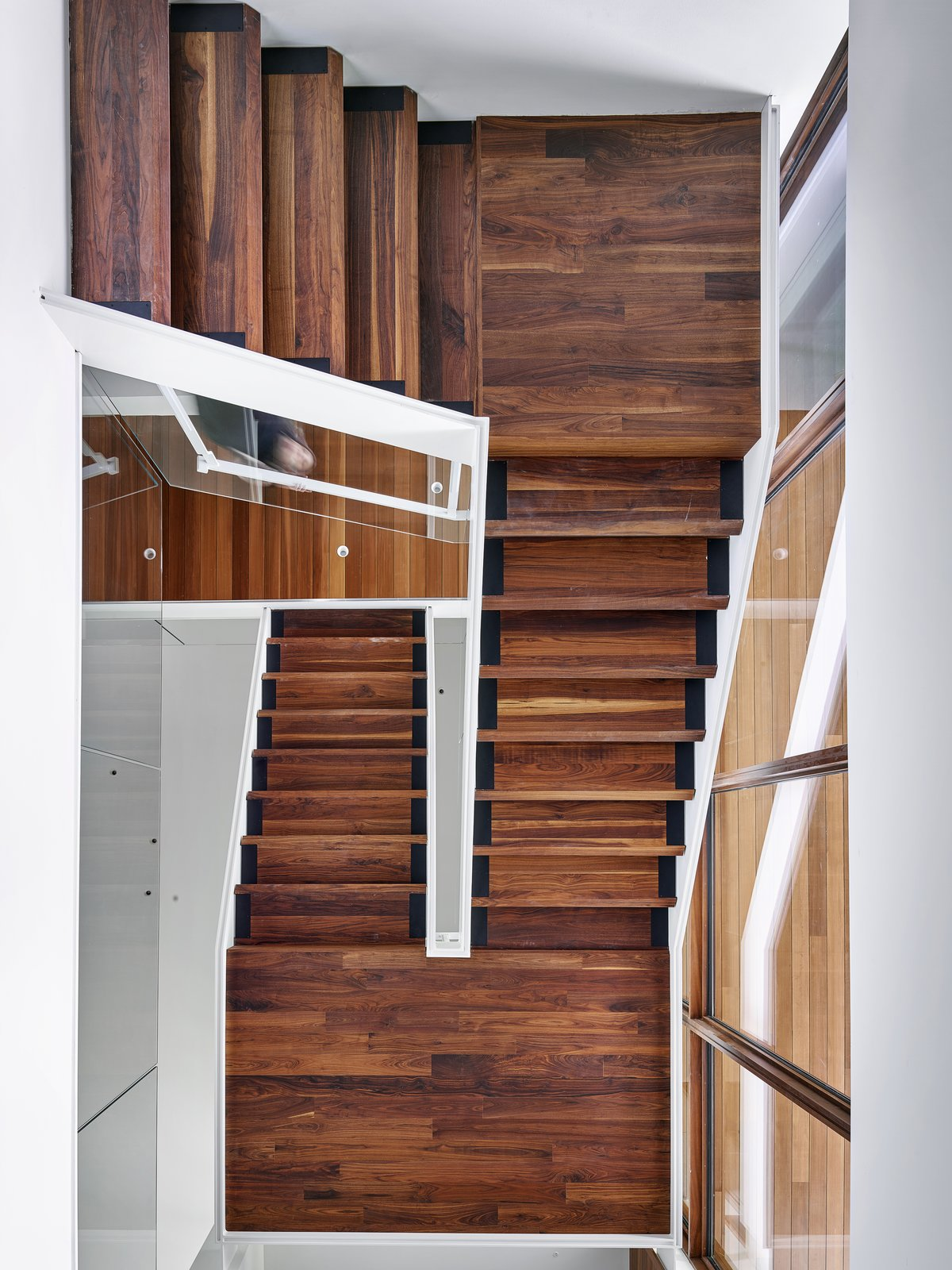 Staircase, Glass Railing, Wood Tread, and Metal Railing The grand, open tread wood staircase vertically connects the three floor plates, while creating an open and transparent connection between them all.   Photo 9 of 23 in A Luminous, Eco-Friendly Abode Is Completed With its Own Modern Art Gallery from Artery House